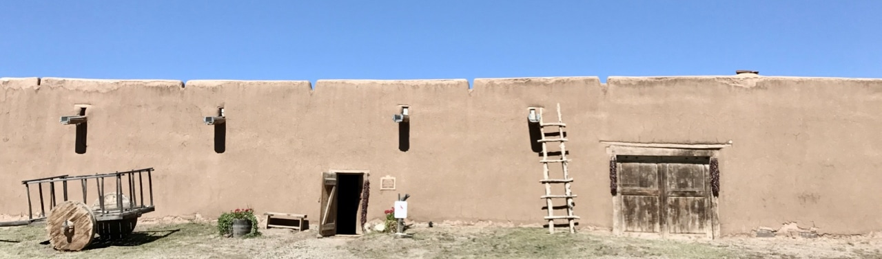 The front of an adobe hacienda, with ladder, rustic cart, and large wooden door