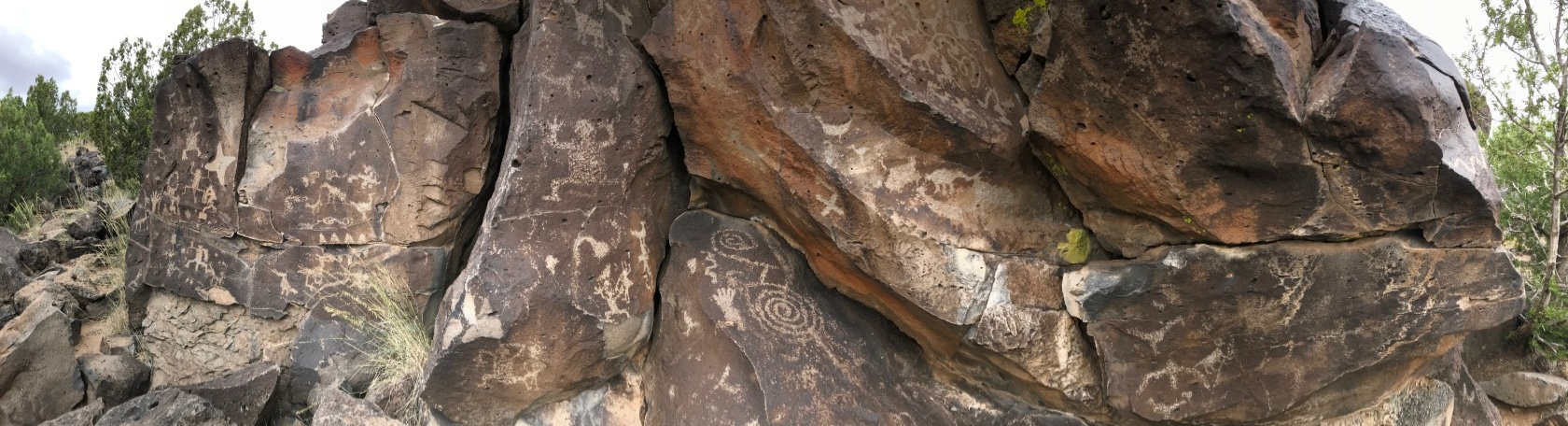 Panorama of tan petroglyphs carved into a brown rock
