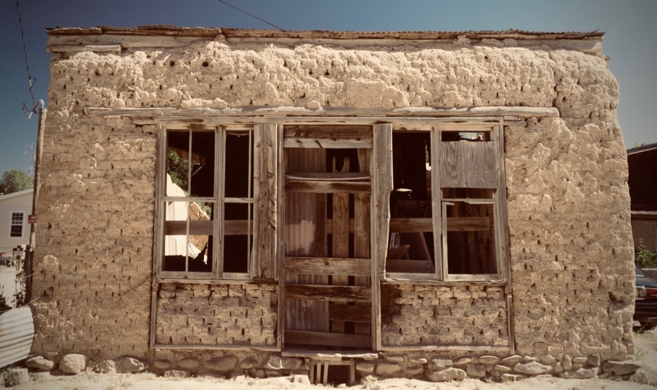 A broken-down mud brick house with no windowpanes and a rotting door