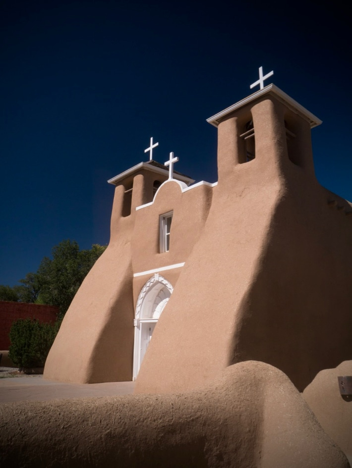 An adobe church, under a blue sky, with white wooden door and crosses, and two bell towers