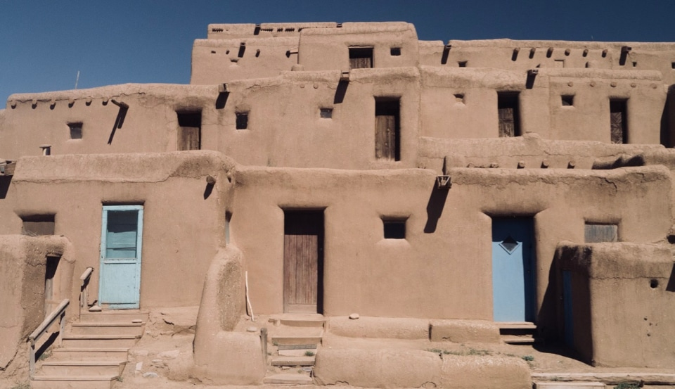 An adobe pueblo, three stories, with exterior doors on each level; doors on first level are light blue
