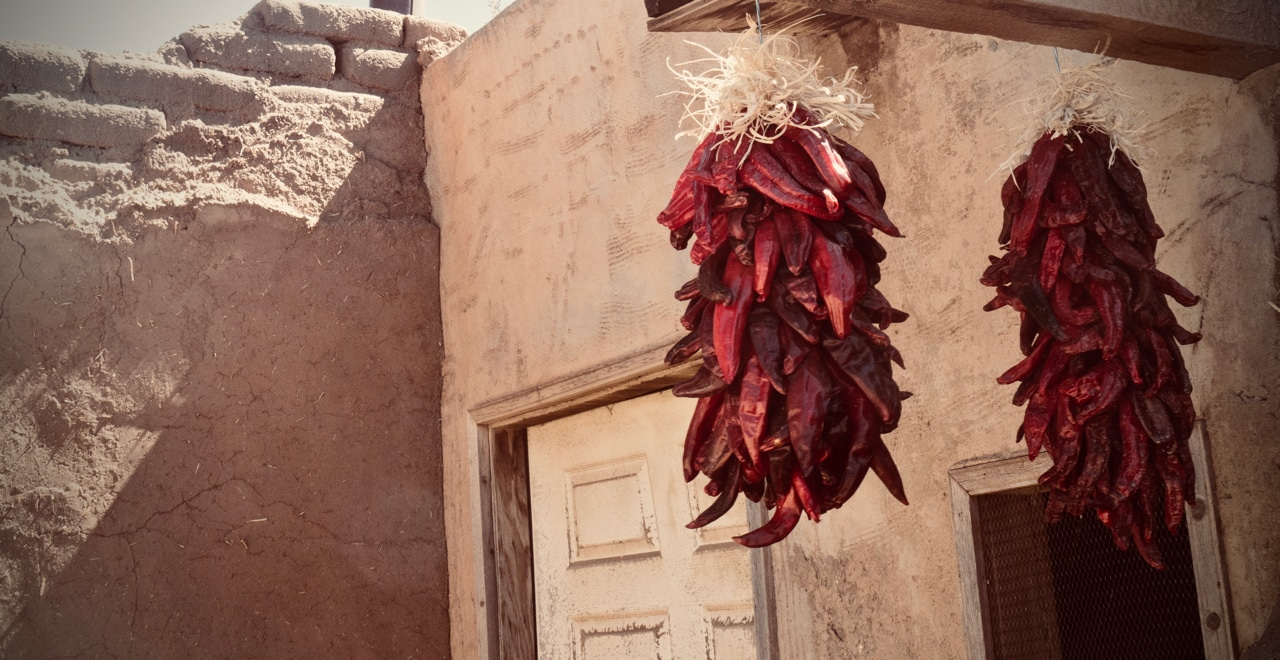 Two bundles of bright red dried chiles hanging in front of a mud brick house