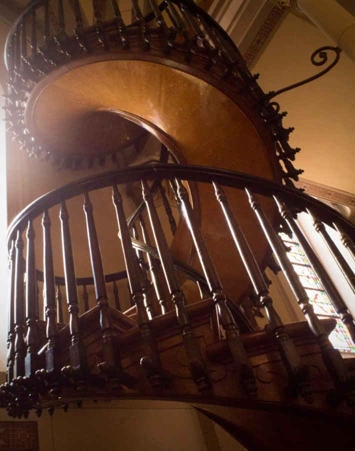 An intricately-carved wooden spiral staircase with no central pillar
