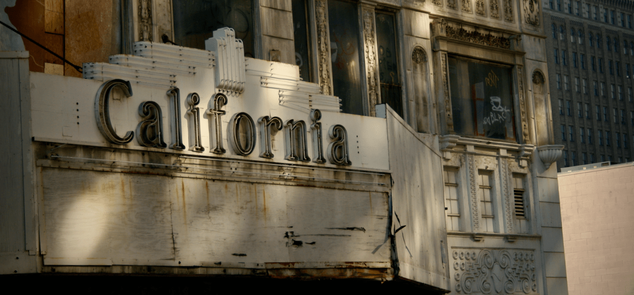Boarded-up theater with 'California' marquee