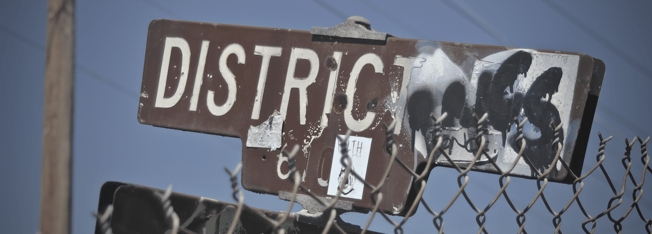 Graffitied street sign reading 'District'