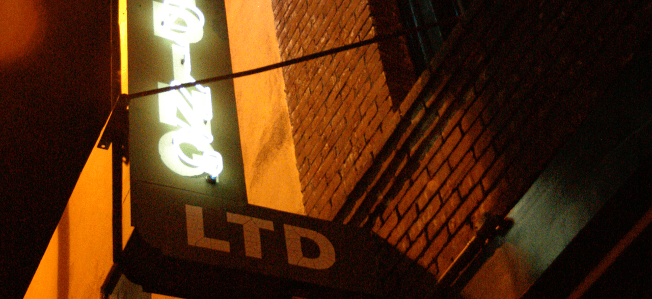 Neon sign on brick building, at night