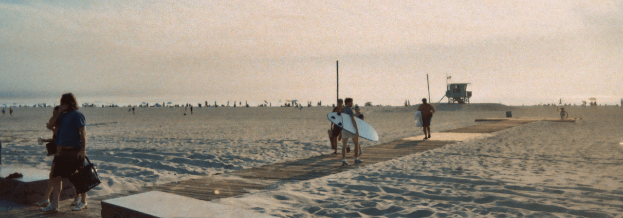 Boardwalk on the beach, with surfers on it
